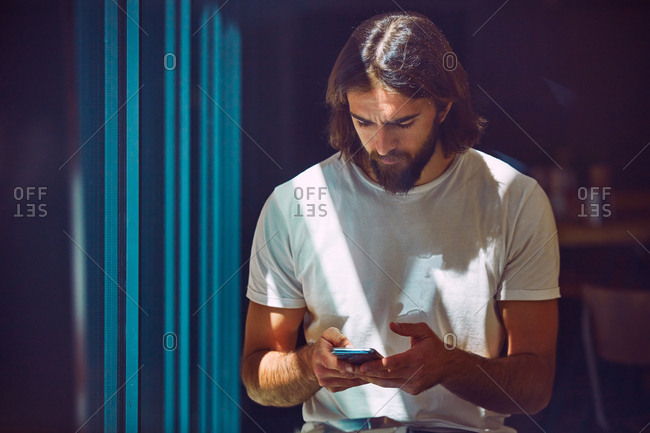 Young bearded handsome man leaning on wall with mobile phone in hands thoughtfully texting