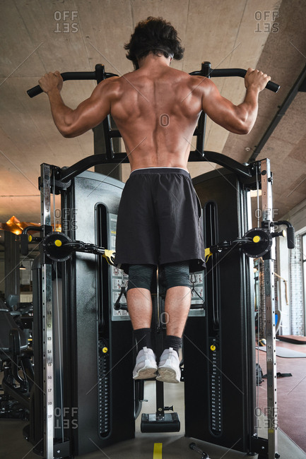 Back view of shirtless ethnic male in shorts performing pull ups on exercise machine while training in gym