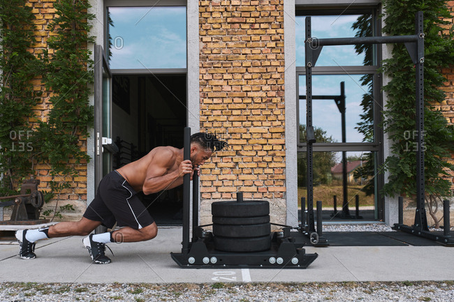 Black guy pulling weights in outdoor gym