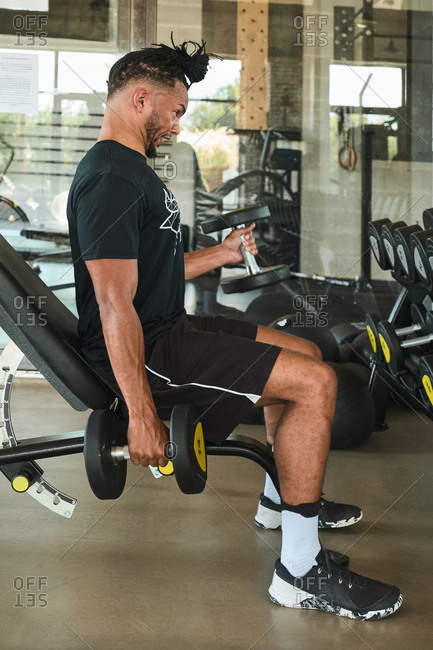 Strong man exercising with dumbbells in gym