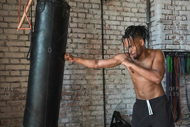 Black guy boxing in gym