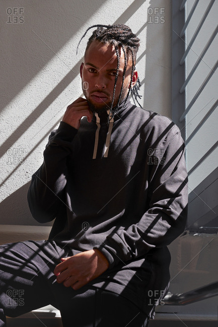 Young African American man sitting on metal handrails, straightening braided hair and looking at camera indoors