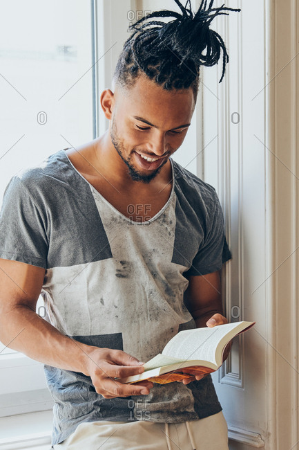 Young African American man with mohawk pigtails standing leaning on windowsill and reading book indoors