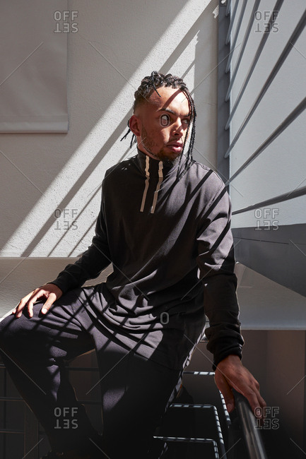 Young African American man sitting on metal handrails, straightening braided hair and looking away indoors