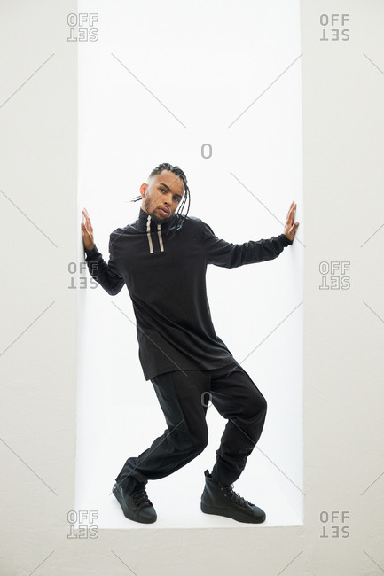 African American man in black clothes with braided hair standing isolated on white background