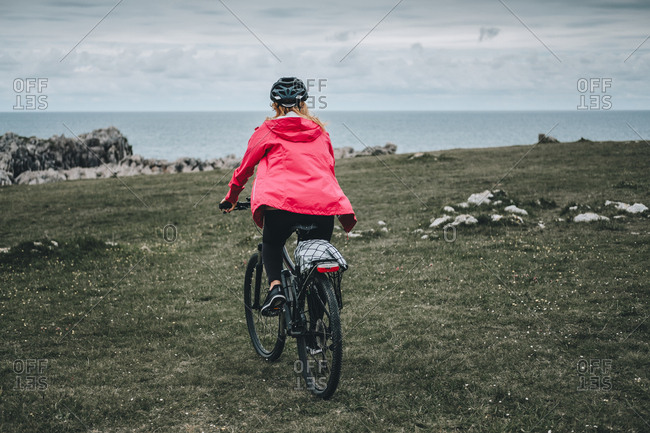 Back view of anonymous woman in black helmet and red jacket cycling on deserted rocky road on cloudy day