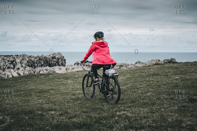 Side view of woman in black helmet and red jacket cycling on deserted rocky road on cloudy day