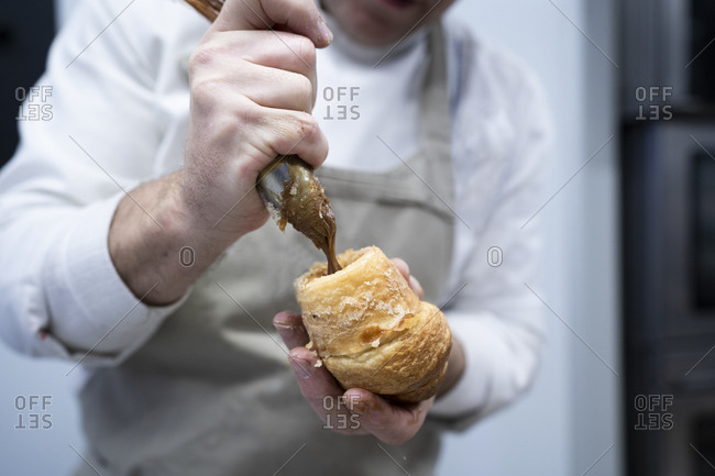 Crop man in apron and white uniform stuffing fresh croissant with chocolate cream indoors