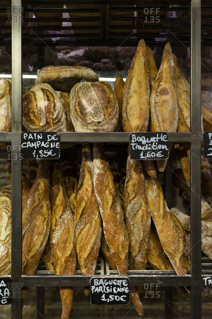 Fresh appetizing baguettes arranged on wooden rack in bakery shop
