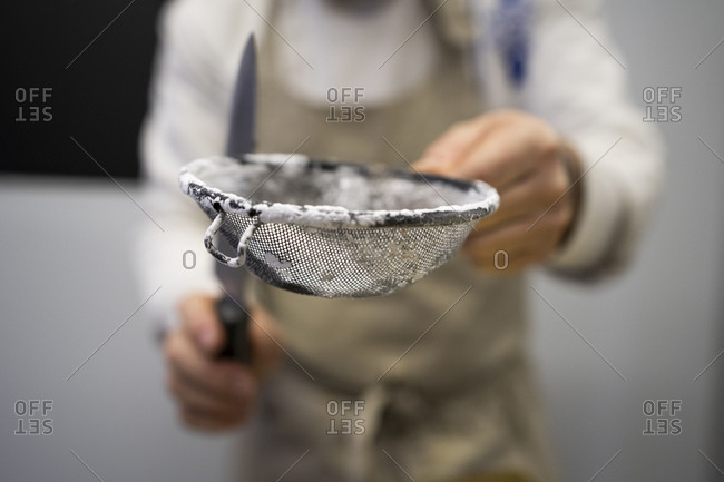 Crop man in apron standing and holding metal sieve with flour and knife on blurred background