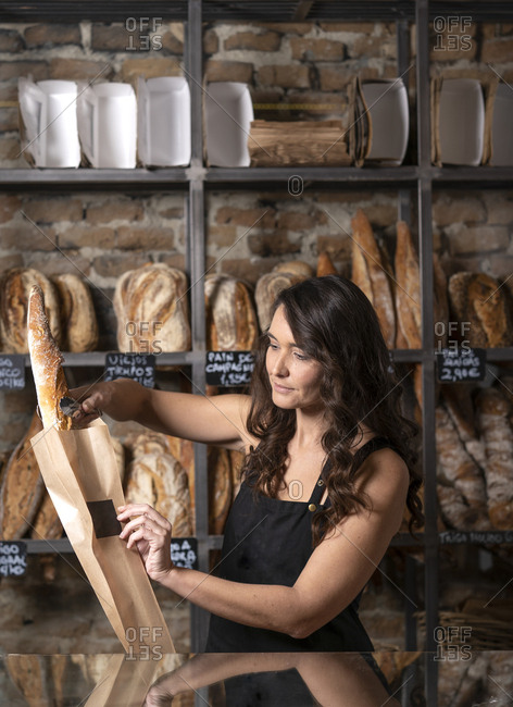 Beautiful woman in black apron putting French baguette in paper bag by metal thongs in bakery