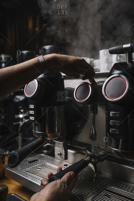 Crop hands of man making coffee by automatic professional equipment in cafe