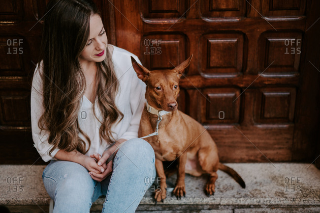 Beautiful casual woman with hound dog sitting on concrete step on street looking away