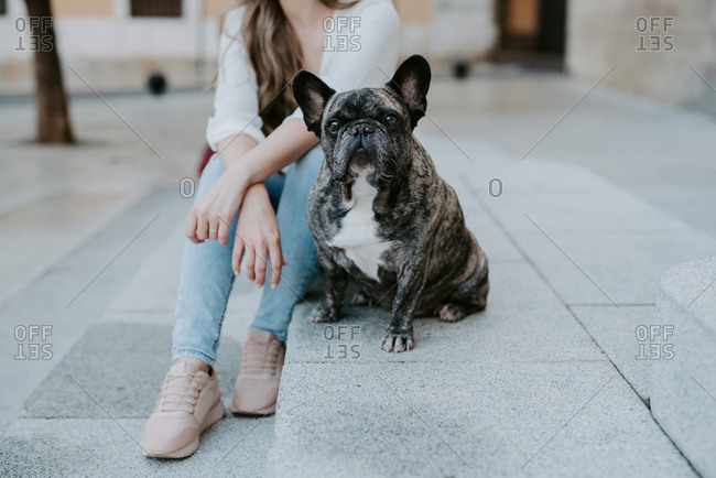 Casual young women sitting on concrete pavement kissing adorable bulldog on street
