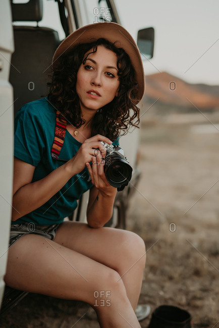Attractive young woman sitting in a cool van holding a photo camera in the middle of nowhere in summer