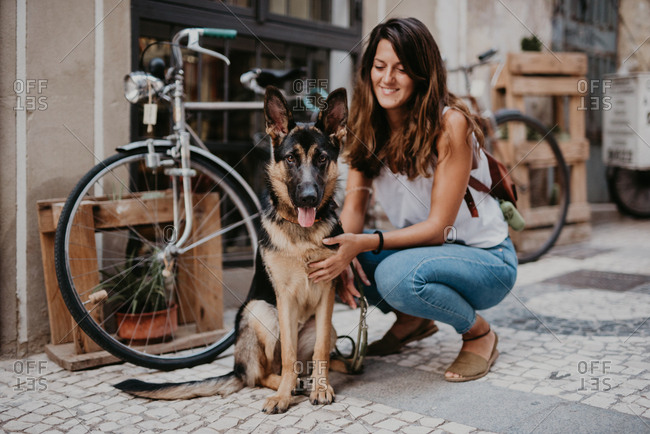 Cute german shepherd standing close bicycle on cobblestone pavement with owner cuddling