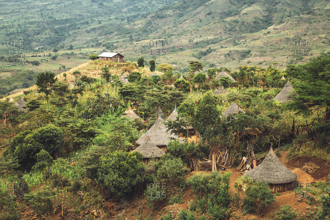 View of small thatched cabins of tribal village in green valley of Ethiopia
