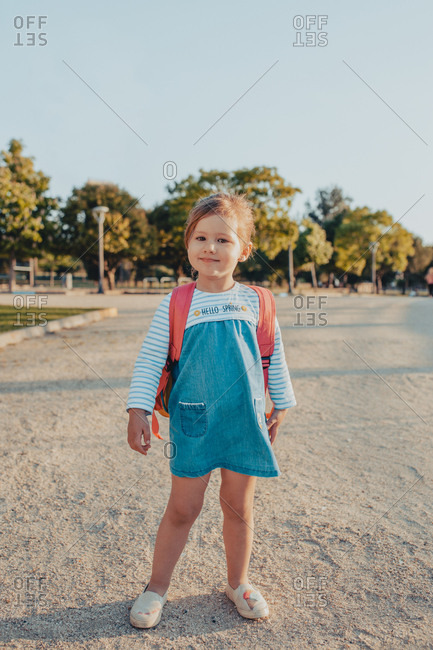 Cute little girl with backpack smiling and looking at camera while standing on sandy ground in park
