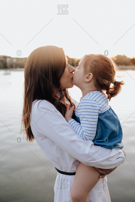 Side view of young woman holding little girl and kissing while standing on shore near rippling water while spending time in park in evening