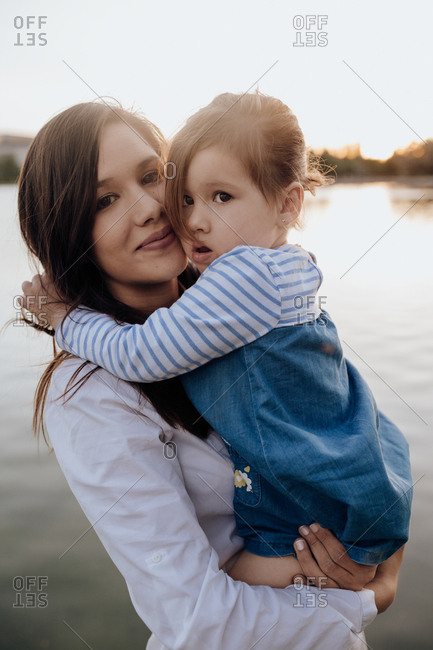 Side view of young woman holding little girl and looking at camera while standing on shore near rippling water while spending time in park in evening