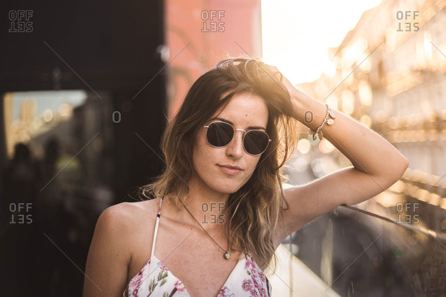 Attractive pensive model with long hair in summer dress on blurred background using sunglasses