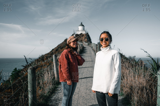Young attractive women in warm clothes looking at camera standing with wide hands outstretched on background of lighthouse on Nugget Point Otago region South Island New Zealand