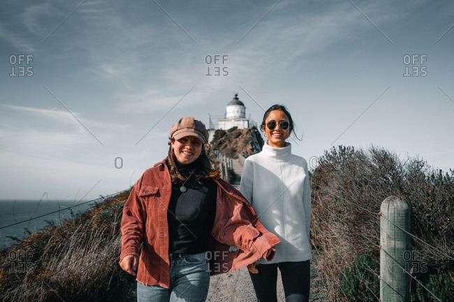 Young attractive women in warm clothes looking at camera walking on background of lighthouse on Nugget Point Otago region South Island New Zealand