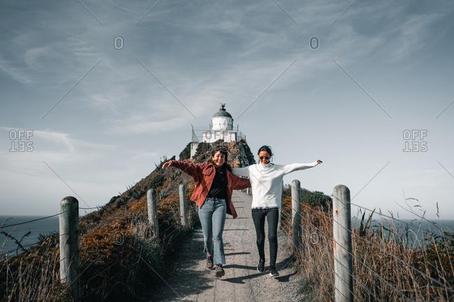 Women standing on bridge spreading arms