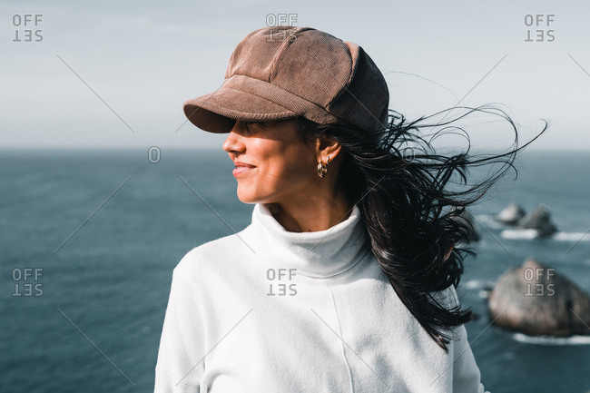 Young attractive woman in light turtleneck and cap smiling and standing on background of breathtaking sea on Nugget Point Otago region South Island New Zealand