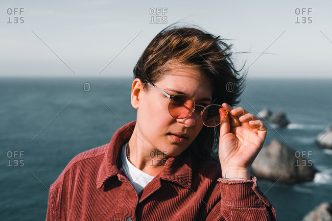 Young attractive woman with sunglasses looking at camera smiling and standing on background of breathtaking sea on Nugget Point Otago region South Island New Zealand