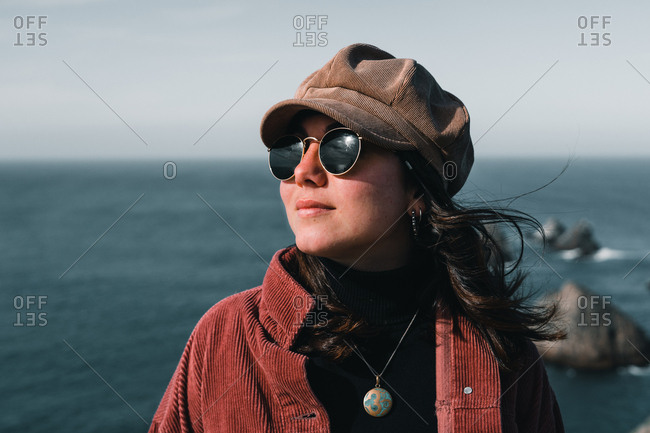 Young attractive woman with sunglasses smiling and standing on background of breathtaking sea on Nugget Point Otago region South Island New Zealand