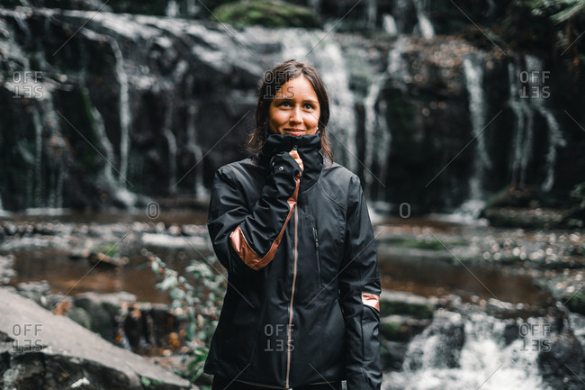 Young attractive woman in black jacket smiling and standing in greenery water stream mountains in Nugget Point Otago region South Island New Zealand