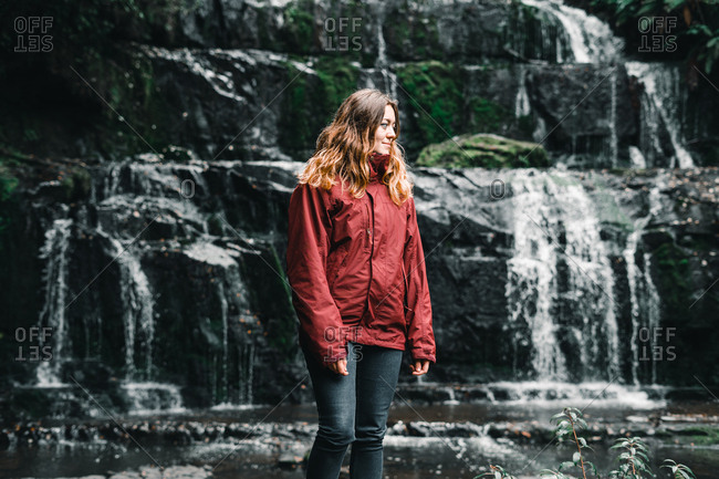 Young attractive woman in red jacket standing in greenery water stream mountains in Nugget Point Otago region South Island New Zealand