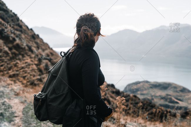 Side view of woman in black and with backpack standing on slope of mountain looking at river landscape