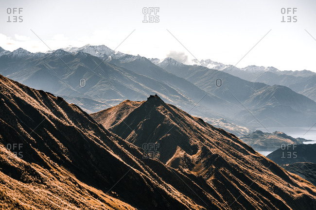 Panoramic view of ridge of mountains with high peaks in sunny haze