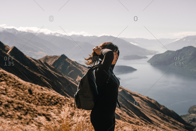Side view of woman in coat standing on high peak of mountains in range looking away with hands on head