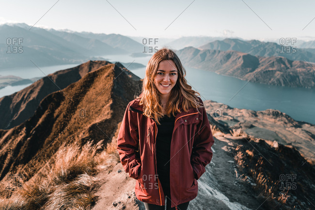Smiling woman in coat standing on high peak of mountains in range smiling and looking at camera