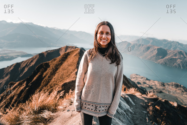 Smiling woman in pullover standing on high peak of mountains in range smiling at camera
