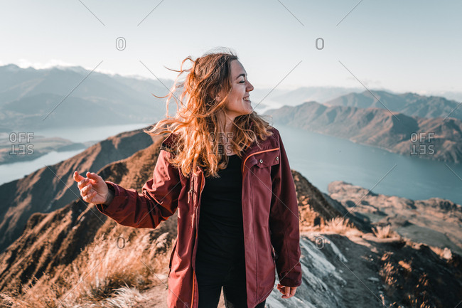 Smiling woman in coat standing on high peak of mountains in range smiling and looking away