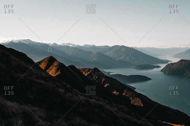 Landscape of tranquil lake water among dark peaky mountains in clouds and sunshine