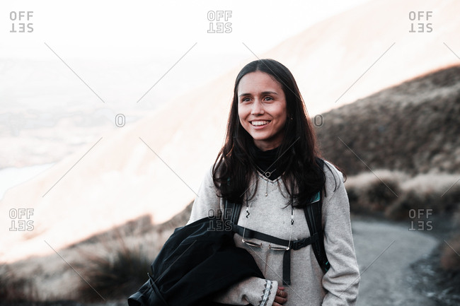 Happy woman with backpack standing on viewpoint of mountain smiling and looking away