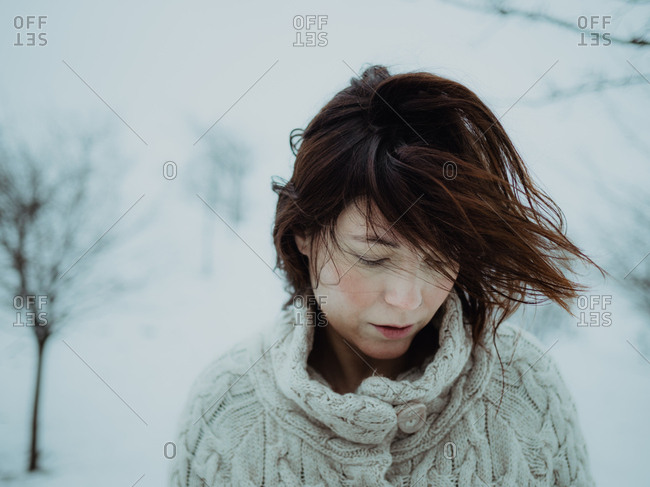Portrait of pensive attractive brunette in white sweater on background of snowy area
