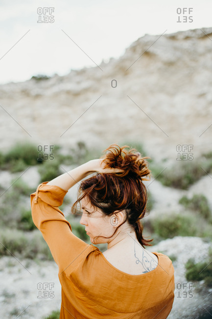 Portrait of thoughtful female model in blouse holding hand above head on background of wild desert landscape
