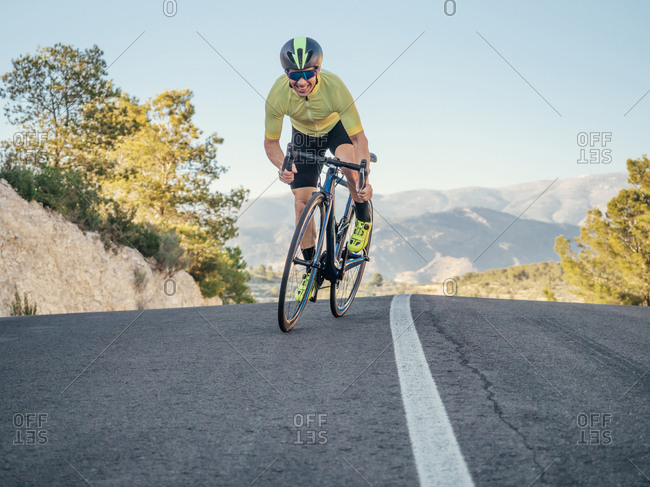 healthy man riding a bicycle on a mountain road in a sunny day