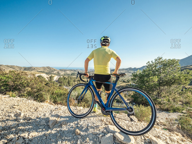 healthy man resting and enjoying the views while riding a bicycle on a mountain road in a sunny day