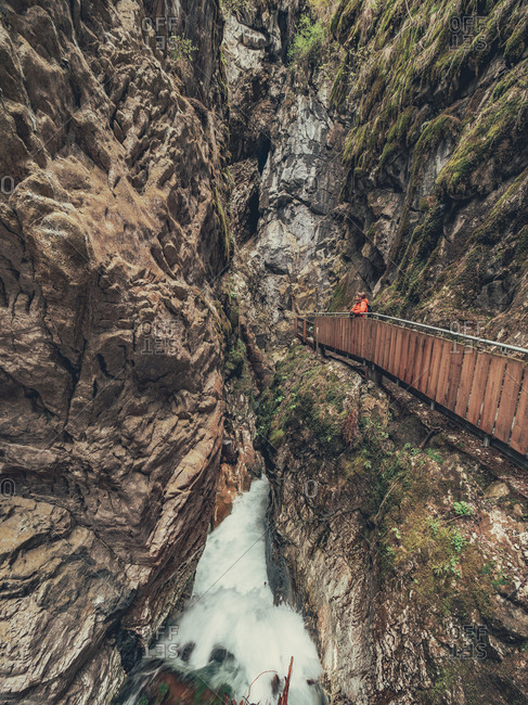 Hiker admiring majestic view of Alps while walking on footbridge in Dolomites, Italy