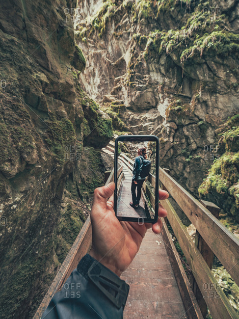 Traveller taking photo of hiker friend while walking on hiking footpath of picturesque area in Dolomites, Italy