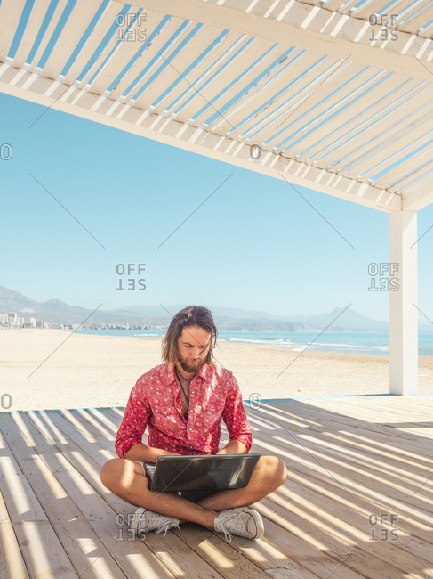 Bearded male browsing modern laptop while sitting in gazebo on sandy beach near sea on sunny day