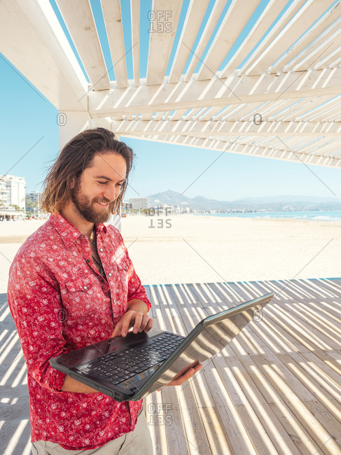 Bearded male browsing modern laptop while standing in gazebo on sandy beach near sea on sunny day