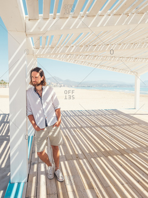 Handsome bearded man keeping hands in pockets and looking away while leaning on pillar of white gazebo on sandy beach